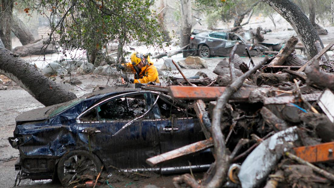 A member of the Long Beach search and rescue team looks for mudslide survivors in a car in Montecito on January 9.  Flooding forced many heavily traveled roads to close.