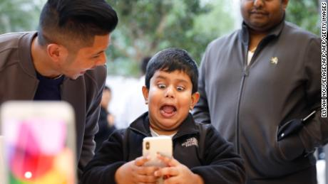 A boy makes faces while testing out the Animoji feature on an iPhone X at the Apple Store Union Square on November 3, 2017, in San Francisco, California. Apple's flagship iPhone X hits stores around the world as the company predicts bumper sales despite the handset's eye-watering price tag, and celebrates a surge in profits. / AFP PHOTO / Elijah Nouvelage        (Photo credit should read ELIJAH NOUVELAGE/AFP/Getty Images)