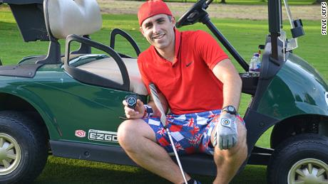 Briton Steve Jeffs poses with a stopwatch after setting a new speed golf world record