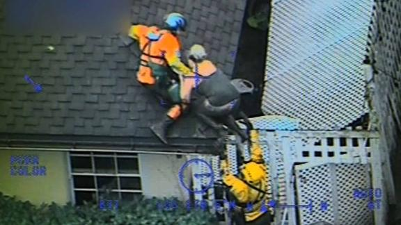 A Coast Guard helicopter crew pulls a person onto a roof after mud overtook a house in Carpinteria.