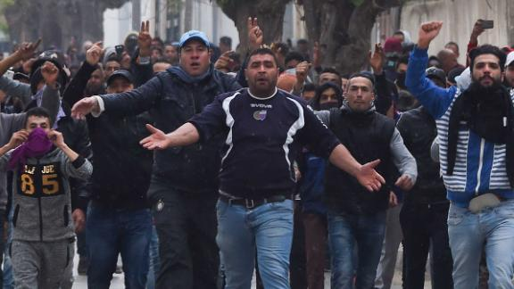 Tunisian protesters gesture toward security forces during clashes in the town of Tebourba on Tuesday following the funeral of a man who died the previous day at an anti-austerity protest.