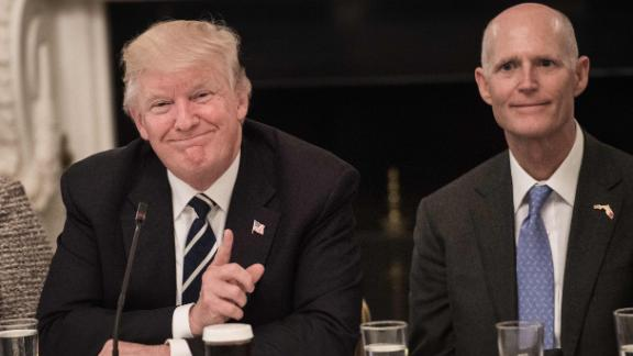 US President Donald Trump smiles at a participant during an infrastructure summit with governors and mayors as Florida Governor Rick Scott (R) looks on in Washington, DC, on June 8, 2017. (NICHOLAS KAMM/AFP/Getty Images)