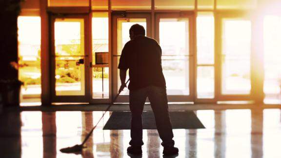 Janitor mopping an office floor, shallow focus, tilt shift image; Shutterstock ID 651210628; Purchase Order: -