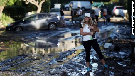 A resident carries her dog as she walks on a mud-covered road after a mudslide on January 10, 2018, in Montecito, California.