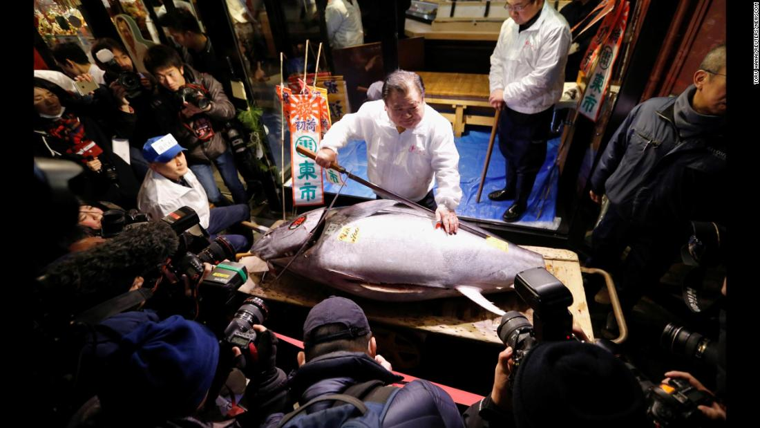 Kiyoshi Kimura, president of a company that runs a sushi restaurant chain, poses with a massive bluefin tuna at the Tsukiji Market in Tokyo on Friday, January 5. The tuna weighed 190 kilograms (419 pounds).