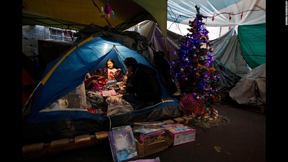 "Julio Dominguez Lozara watches his daughter Cynthia and her two sisters play with Three Kings Day gifts in a Mexico City tent camp on Saturday, January 6. They have been living in the tent camp since their apartment was damaged in a <a href=""http://www.cnn.com/interactive/2017/09/world/mexico-quake-cnnphotos/"" target=""_blank"">September earthquake.</a>"