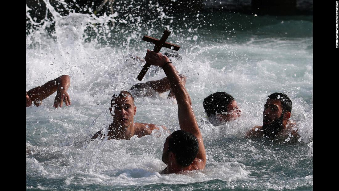 A man holds a cross during a competition to retrieve it from the water during Epiphany celebrations in Zygi, Cyprus, on Saturday, January 6.