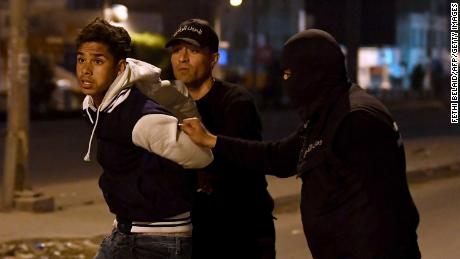 Tunisian security forces detain a protester late Wednesday on the outskirts of the capital, Tunis.