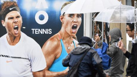 People shelter with umbrellas from the rain ahead of the Australian Open tennis tournament in Melbourne on January 13, 2018. / AFP PHOTO / WILLIAM WEST / -- IMAGE RESTRICTED TO EDITORIAL USE - STRICTLY NO COMMERCIAL USE --        (Photo credit should read WILLIAM WEST/AFP/Getty Images)