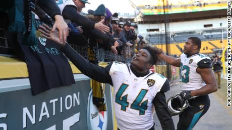 Myles Jack and Calais Campbell of the Jaguars high five fans after defeating the Steelers.