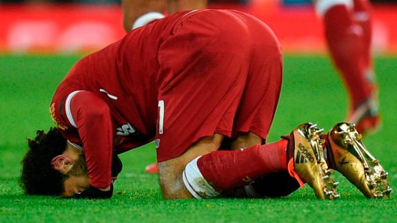 Liverpool's Egyptian midfielder Mohamed Salah puts his head on the pitch after scoring his team's fourth goal.
