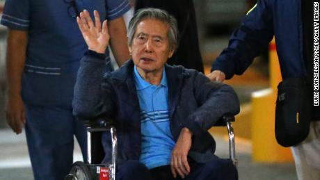 Peru's former President Alberto Fujimori waves to supporters as he is wheeled out of the Centenario Clinic in Lima on January 04, 2018, where he was hospitalised for the last twelve days and where he received a Christmas' eve pardon from President Kuczynski. Fujimori was pardoned days after his son Kenji abstained from voting on Kuczynskis impeachment, drawing other lawmakers with him to deny the opposition the votes necessary to remove the president from office over corruption allegations.  / AFP PHOTO / LUKA GONZALES        (Photo credit should read LUKA GONZALES/AFP/Getty Images)