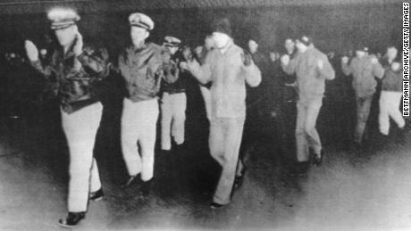 The USS Pueblo crew seen in a propaganda photo released by their captors after the ship was seized by North Korea.