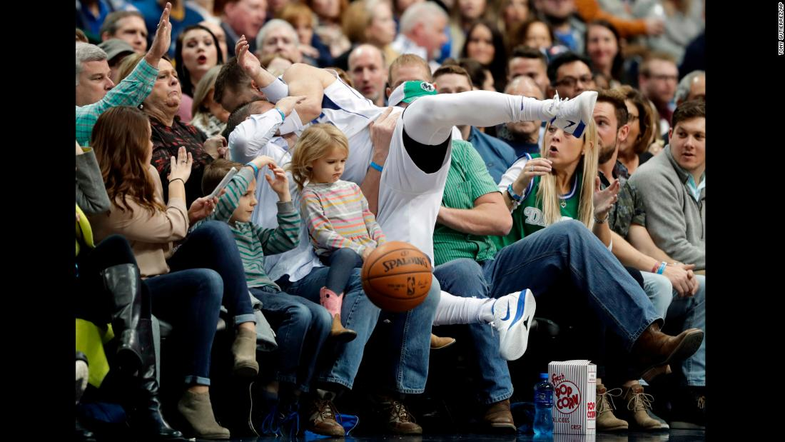 Fans brace as Dallas Mavericks' J.J. Barea lands in their laps while chasing a loose ball at an NBA basketball game against the Orlando Magic on Tuesday, January 9.<br />