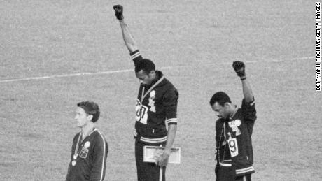 Tommie Smith, center, and John Carlos, gold and bronze medalists in the 200-meter sprint at the 1968 Olympic Games, raise their fists on the medal stand.