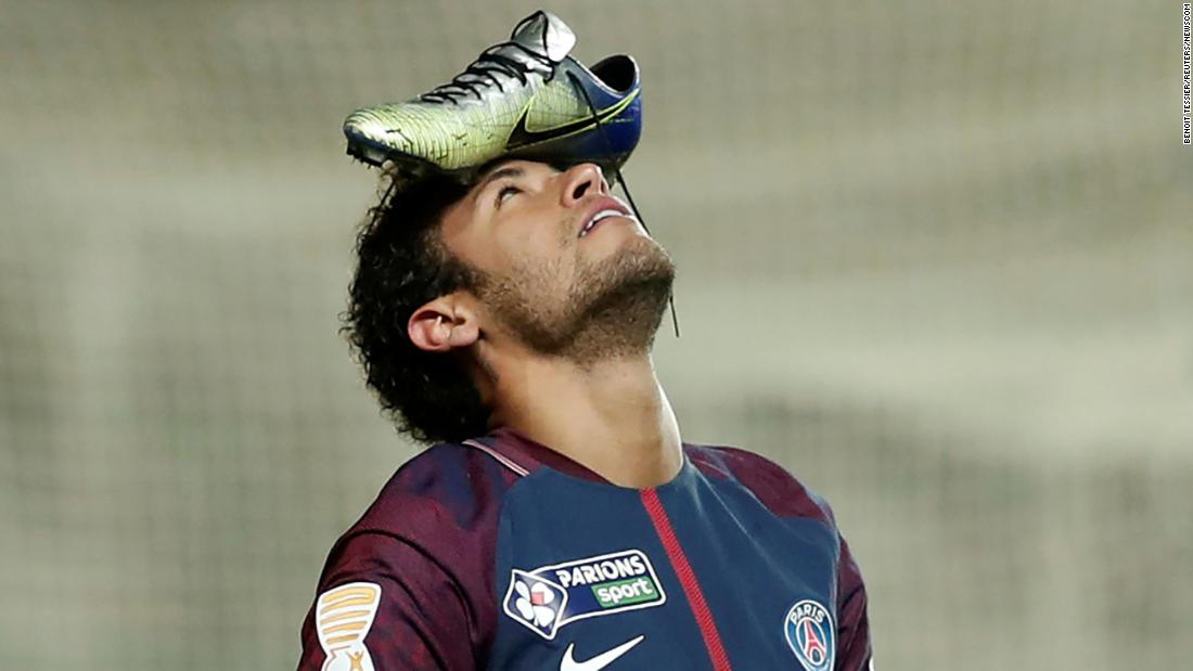 Paris Saint-Germain's Neymar balances his boot on his head to celebrate scoring a penalty kick during the French League Cup quarter-final football match on January 10 in Amiens, northern France.