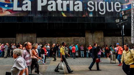"People queue to withdraw money from an ATM in Caracas on November 14, 2017. Venezuela has been declared in ""selective default"" by Standard and Poor's after failing to make interest payments on bond issues as it tries to refinance its $150 billion foreign debt. / AFP PHOTO / Juan BARRETO        (Photo credit should read JUAN BARRETO/AFP/Getty Images)"