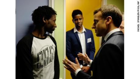 French President Emmanuel Macron talks to Ahmed Adam, left, from Sudan during his visit to a migrant center in Croisilles, northern France.