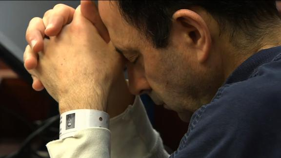 Larry Nassar rests his head on his hands Tuesday during his sentencing for seven counts of criminal sexual conduct.
