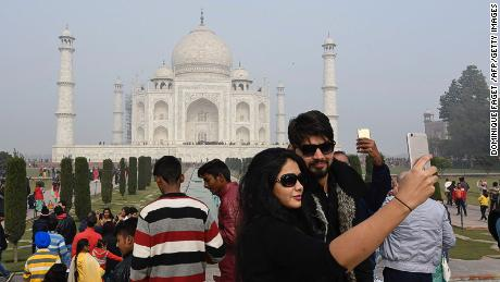 Tourists take selfies against the backdrop of the Taj Mahal.
