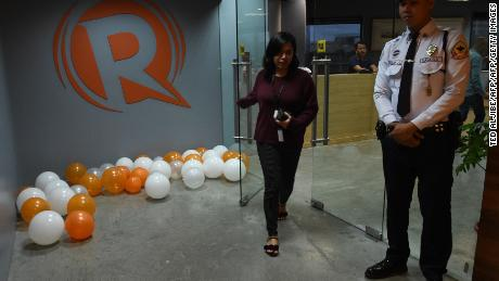 An employee of online portal Rappler heads out from their editorial office in Manila on January 15, 2018, while a private security guard stands.