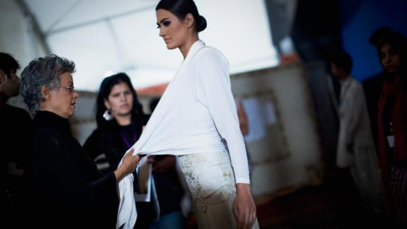 Pakistani designer Maheen Khan makes fiinishing touches on a model wearing one of her creations during Fashion Pakistan Week in November 2009 in Karachi.