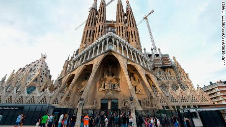 "Tourists walk by the ""Sagrada Familia"" (Holy Family) basilica in Barcelona on August 19, 2017, two days after a van ploughed into the crowd, killing 13 persons and injuring over 100. Drivers have ploughed on August 17, 2017 into pedestrians in two quick-succession, separate attacks in Barcelona and another popular Spanish seaside city, leaving 14 people dead and injuring more than 100 others. / AFP PHOTO / LLUIS GENE        (Photo credit should read LLUIS GENE/AFP/Getty Images)"