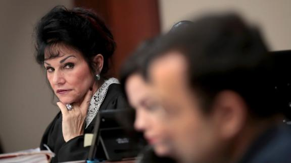 Judge Rosemarie Aquilina (L) looks at Larry Nassar (R) as he listens to a victim