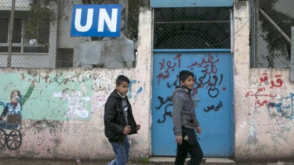 Palestinian children walk outside of the United Nations