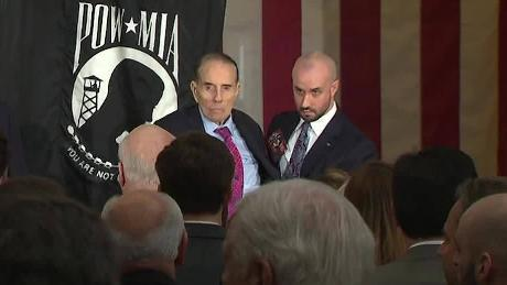 Bob Dole gets assistance to stand for the flag