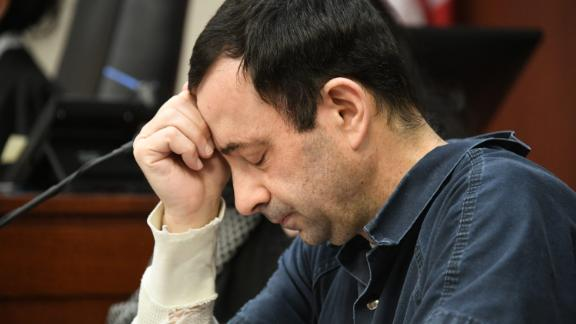 "A victim makes her ""impact statement"" to Larry Nassar during a sentencing hearing as he puts his head down in front of Judge Rosemarie Aquilina in district court on Tuesday, Jan. 16, 2018, in Lansing, Mich. Nassar has pleaded guilty to molesting females with his hands at his Michigan State University office, his home and a Lansing-area gymnastics club, often while their parents were in the room. (Dale G. Young/Detroit News via AP)"