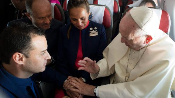 Pope Francis marries flight attendants Carlos Ciuffardi, left, and Paola Podest, center, during a flight from Santiago, Chile, to Iquique, Chile, Thursday, Jan. 18, 2018. Pope Francis celebrated the first-ever airborne papal wedding, marrying these two flight attendants from Chile
