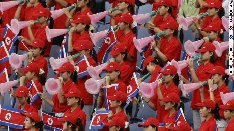 North Korean cheering squad hold their national flag and cheer, 04 September 2005.
