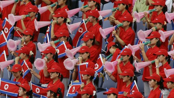 North Korean cheering squad hold their national flag and cheer 04 September 2005.