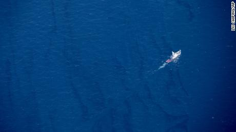 In this Jan. 15, 2018, aerial photo released by China's Xinhua News Agency, a boat moves through an oil slick on the surface of the East China Sea left by oil leaking from the sunken Iranian tanker ship Sanchi.