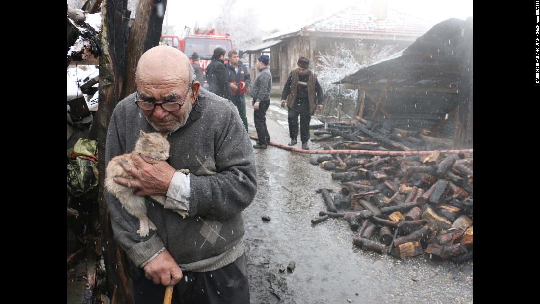 "Ali Mese, 83, holds his cat after firefighters saved the animal in Bolu, Turkey, on Wednesday, January 17. Mese accidentally started a fire at his home while trying to light his heating stove with gasoline, <a href=""https://www.dailysabah.com/life/2018/01/17/old-man-in-tears-hugs-beloved-cat-as-his-house-burns-down"" target=""_blank"">according to Turkey's pro-government Daily Sabah newspaper</a>."
