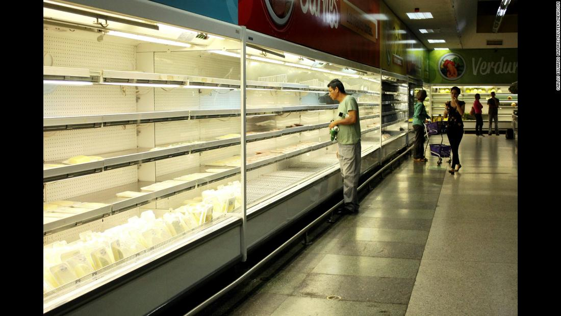"A man selects a deli item from a nearly empty refrigerator at a supermarket in San Cristóbal, Venezuela, on Tuesday, January 16. Supermarkets and other stores have become scenes of chaos as <a href=""http://money.cnn.com/2018/01/17/news/economy/venezuela-cash-crisis/index.html"">Venezuela's currency, the bolivar, has become virtually worthless</a> during the country's economic crisis."
