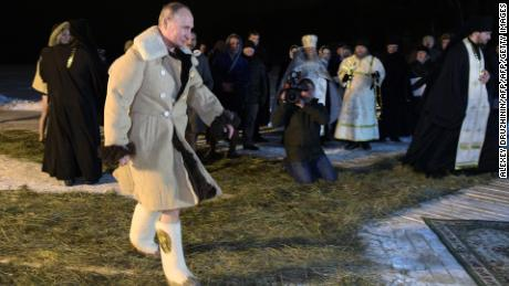 Putin wore a thick coat and boats before stripping off to take the plunge.