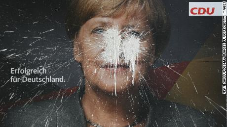 Chancellor Angela Merkel, pictured here on a vandalized campaign billboard, has struggled to build a new government since elections in September.