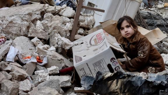 Five-year-old Ashwaq sits on the rubble of her former home in Mosul