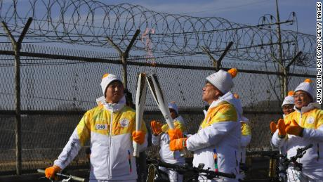 Torchbearers 'kiss' with their torches to pass the Olympic flame in front of a military fence on the road leading to the Panmunjom truce village on January 19, 2018.