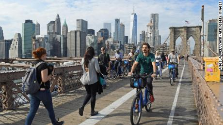 People bike on the Brooklyn Bridge from downtown Manhattan on November 3, 2017 in New York. / AFP PHOTO / ANGELA WEISS        (Photo credit should read ANGELA WEISS/AFP/Getty Images)