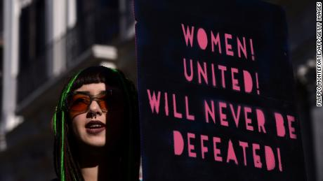 "A woman holds a sign reading ""Women united! Will never be defeated!"" during a demonstration in downtown Rome."