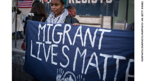 "A woman in Rome holds a sign reading ""Migrant Lives Matter."""