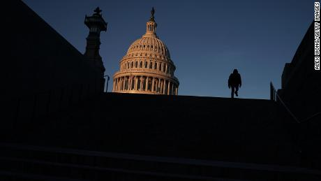 A man walks up the steps in front of the U.S. Capitol in the morning hours January 20 in Washington, D.C.