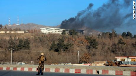 An Afghan security official stands guard as black smoke rises from the Intercontinental Hotel Sunday.