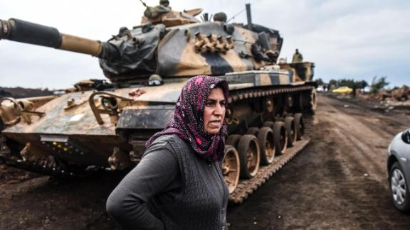 A Turkish villager stands next to Turkish army tanks as soldiers gather close to the Syrian border.