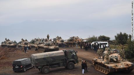 Villagers watch as Turkish army tanks and soldiers gather near the Syrian border on January 21.