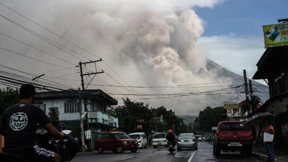 Motorists travel on a highway as Mount Mayon shot up a giant mushroom-shaped cloud as it continues to erupt near Camalig town, near Legazpi City in Albay province, south of Manila on January 22, 2018.