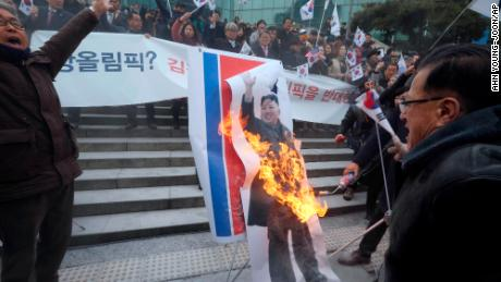 Protesters set a portrait of North Korean leader Kim Jong Un on fire Monday.